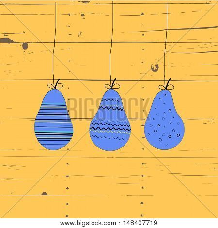 three purple pear with ornaments on strings. Wooden background