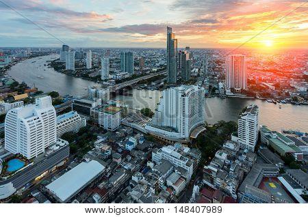 Aerial view of Bangkok modern office buildings condominium in Bangkok city downtown with Chao Phraya River during sunset sky Bangkok Thailand