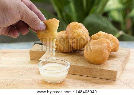 Hand hold deep fried dough bun dip in sweetened condensed milk