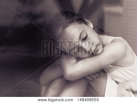 Sad little girl sitting on the window sill and looking out the window