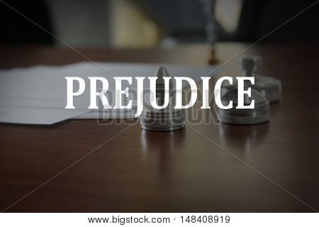 PREJUDICE. Metal stamps and ink pad on wooden table