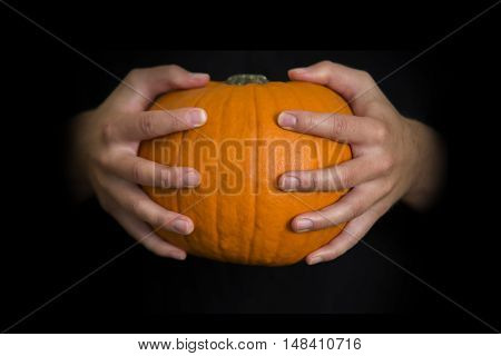 Hands Holding A Halloween  Pumpkin, With Copy Space On Black