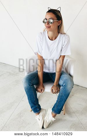 Woman wearing blanc t-shirt, sunglasses jeans and sneakers sitting on chair, toned photo, front tshirt mockup on model, hipster style