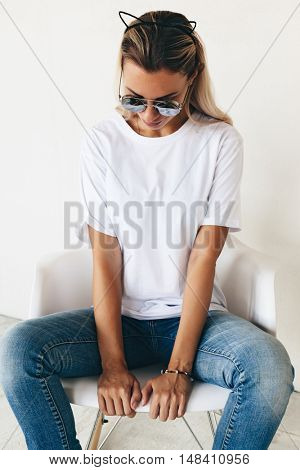 Woman wearing blanc t-shirt, sunglasses and jeans sitting on chair, toned photo, front tshirt mockup on model, hipster style