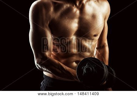 Focus on right torso. Dark contrast shot of young muscular fitness man torso and arm. Bodybuilder with beads of sweat training in gym. Working out with dumbbells on black background