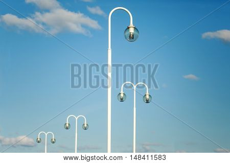 White modern lamp posts against blue sky with clouds. Place for text.