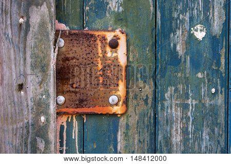 Vintage rusty metal plate on old wooden weathered door