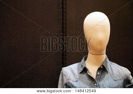 Faceless female mannequin wearing cheap casual jean jacket at shopping mall. Bald dummy close-up with copy space