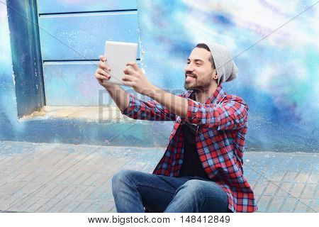 Young latin man taking a selfie with tablet. Urban scene.