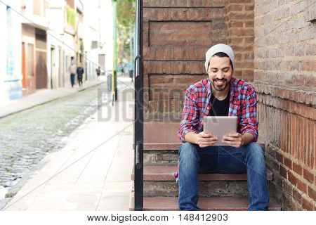 Young latin man using a tablet at the street.