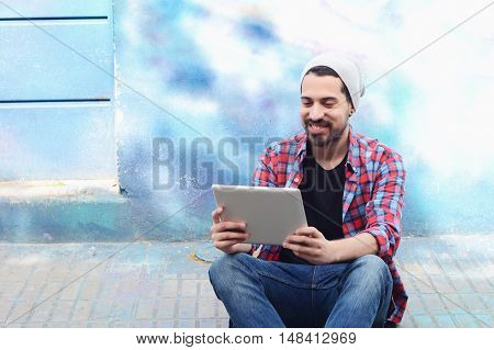 Young latin man touching at tablet at the street.