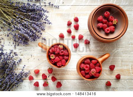 pottery with berries and lavender on wooden table top view
