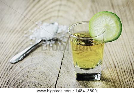 Tequila shot with lime and salt on rustic wooden background.