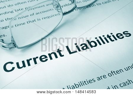 Paper with sign current liabilities and a pen. Business concept.