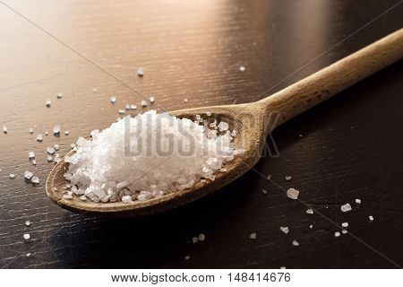 wood kitchen spoon with salt on black table