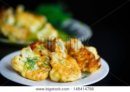 cauliflower fried in batter on a black background