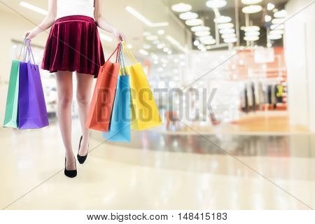 Woman shopping in shopping mall and carrying shopping bags.