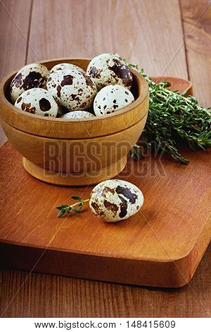 Quail eggs with a thyme in a wooden cup on a brown kitchen board.