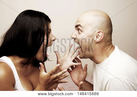 Young couple - man and woman screaming at each other before marriage divorce