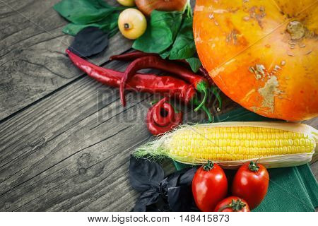 Fresh vegetables on a dark table. Autumn background. Healthy eating. Pumpkin, bell peppers, paprika, tomatoes, basil, corn cob Top view