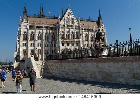 Budapest Hungary - 20 August 2016: Tourists stroll the waterfront of the Danube near the Parliament during the celebration of St. Stephen's Day.
