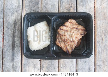 grilled pork and sticky rice in box on wood table