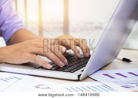 Businessman's hands typing on laptop keyboard and analyze marketing chart.