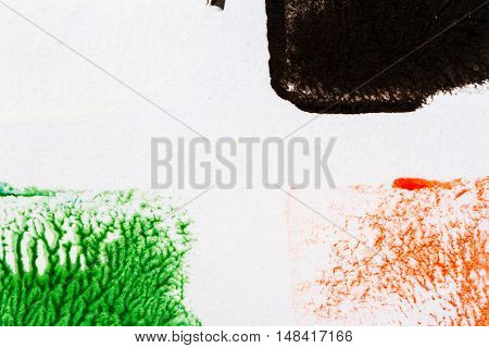 Closeup view of abstract hand painted black green and red acrylic art background on paper texture