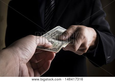 Two business people hands and money background.
