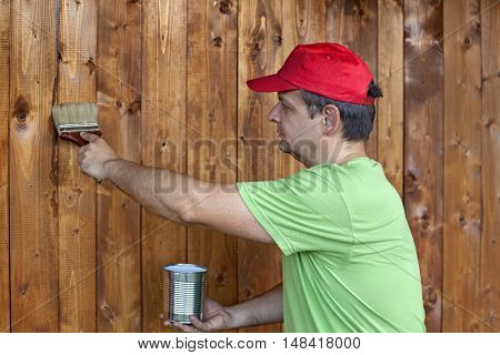 Man painting wooden wall - renovating the wood shed