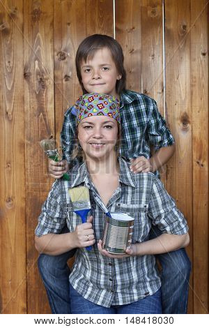 Boy helping his mother painting the tool shed - holding brushes and having fun