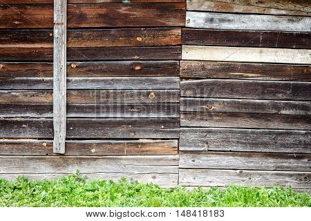 Old gray wooden wall and green grass