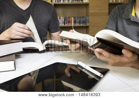 Young man and woman reading book in library.People studying together in a library