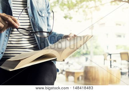 Woman use glasses to read a book in library cafe in the morning