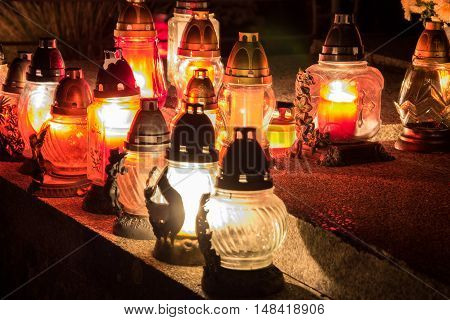 Votive candles lantern burning on the graves in Slovak cemetery at night time. All Saints' Day. Solemnity of All Saints. All Hallows eve. 1st November. Feast of All Saints. Hallowmas. All Souls' Day