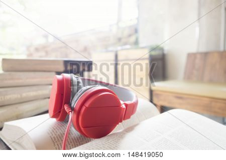 Red headphone on book in cafe or library. Soft focus and soft sunlight in the morning feel relax.
