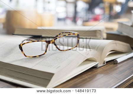 glasses on opening book in library or cafe