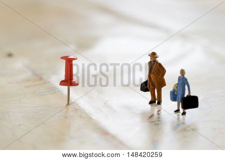 Figture traveler with red pushpin and a map travel concept.