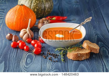 Pumpkin And Carrot Soup With Cream And Parsley On Blue Background