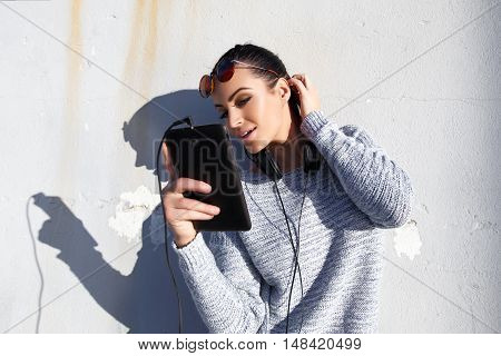 Young stylish hipster woman with tablet and headphones outdoor