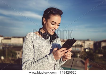 Young stylish woman with headphones and tablet outdoor selecting music from playlist