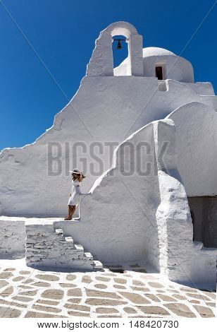 Woman in white at the Paraportiani Church of Mykonos, Greece