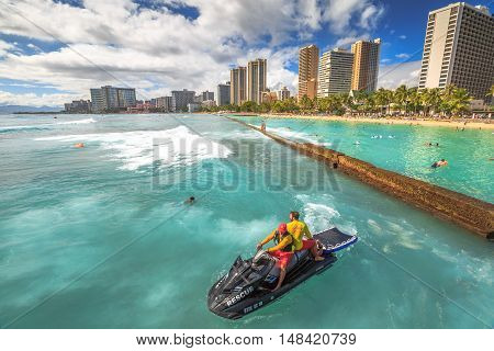 Waikiki, Oahu, HI - August 27, 2016: Waikiki Beach skyline in Kuhio Beach section protected by a concrete wall. Two lifeguards in jet ski to monitor the area over the wall where powerful waves break.