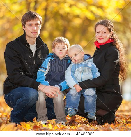 Happy family concept. Autumn background. Lovely father, mother and sons, carefree family rest on the foliage in the autumn park