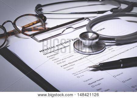 doctor desktop with stethoscope clipboard with medical records form.