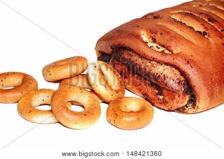 Roll with poppy seeds and bagels on white background