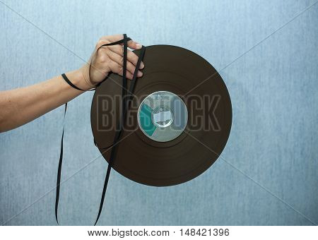Female hand holding a reel to reel tape against the blue background