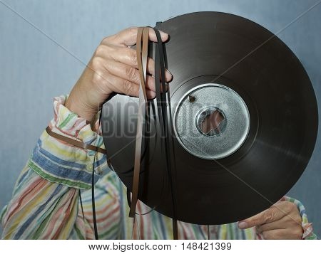DJ or sound engineer holding a reel to reel tape closeup front shot