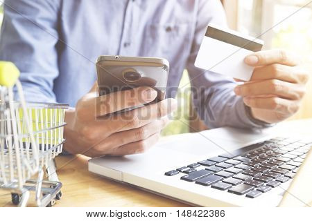 Man using laptop and mobile phone to online shopping and pay by credit card. Vintage tone Retro filter effect Soft focus Low light.(selective focus)