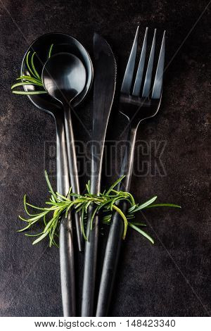 Set of black cutlery knife, spoon, tea spoon, fork with rosemary on black stone background. Top view